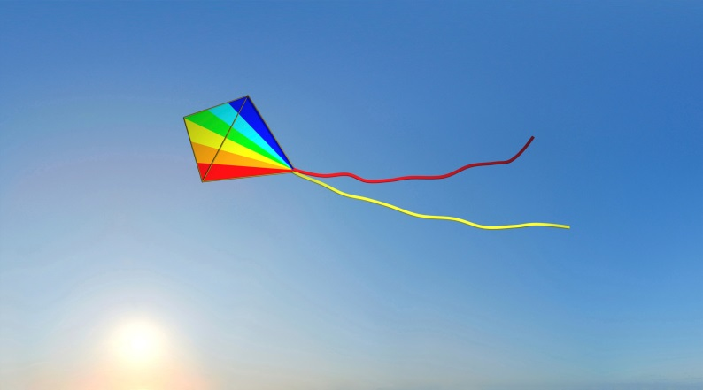 rainbow striped kite flying in the blue sky
